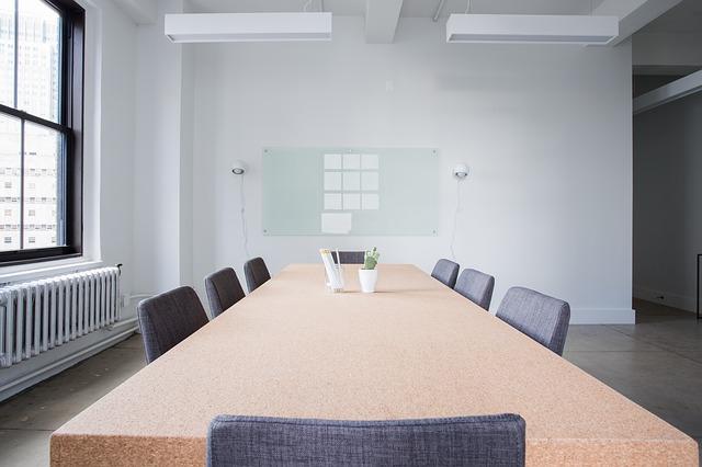 velký stůl, šedé židle, konferenční místnost